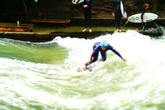 Surfers ποταμών στον ποταμό Eisbach στη μέση της ευρωπαϊκής πόλης Στοκ φωτογραφίες με δικαίωμα ελεύθερης χρήσης