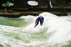 Surfers ποταμών στον ποταμό Eisbach στη μέση της ευρωπαϊκής πόλης Στοκ Εικόνα