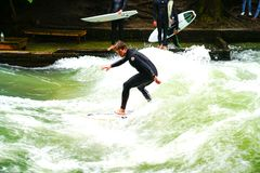 Surfers ποταμών στον ποταμό Eisbach στη μέση της ευρωπαϊκής πόλης Στοκ φωτογραφία με δικαίωμα ελεύθερης χρήσης
