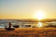 Surfers που μπαίνει στο ηλιοβασίλεμα στοκ φωτογραφίες