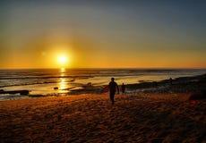 Surfers που μπαίνει στο ηλιοβασίλεμα στοκ φωτογραφία
