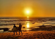 Surfers που μπαίνει στο ηλιοβασίλεμα στοκ φωτογραφίες με δικαίωμα ελεύθερης χρήσης