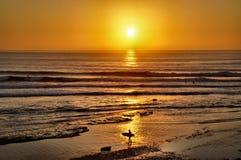 Surfers που μπαίνει στο ηλιοβασίλεμα στοκ εικόνες
