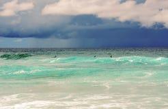Surfers που σκιαγραφείται ενάντια στο θυελλώδη ουρανό Στοκ Φωτογραφία