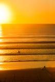 Surfers στην παραλία στο ηλιοβασίλεμα Στοκ Φωτογραφίες