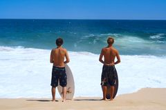 Surfers. Young surfers watching the waves Royalty Free Stock Image