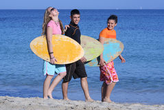 Surfers. 3 teens going surfing Stock Photo