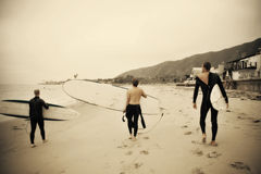 Surfers. Three surfers get ready to hit the waves on a summer morning. Dramatic Sepia Toned photo Stock Image