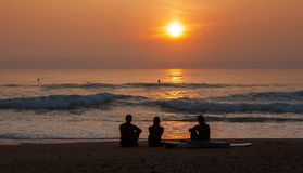Surfers Admiring the Sunset. Image of the silhouettes of three surfers admiring the sunset at the coastline Royalty Free Stock Images