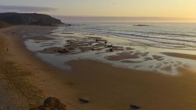 Surfers on Amado beach on sunset stock video