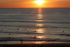 Surfers attendant une vague près de la plage au coucher du soleil Images stock