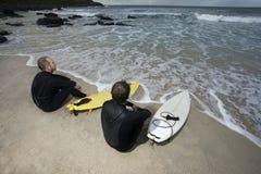 Surfers avec des planches de surf regardant la mer Photo stock