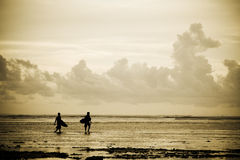 Surfers on the beach. A silhouette shot of a couple of surfers on the beach during sunset Royalty Free Stock Images