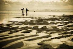 Surfers at the beach. Two surfers at the beach during sunset Stock Photos