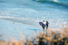 Surfers on a beach Stock Photography