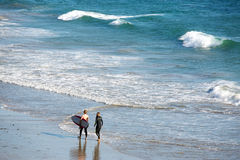 Surfers on a beach Stock Images