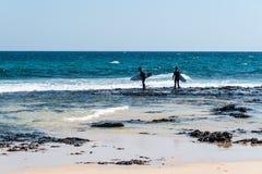 Surfers in the beach of Corralejo Bay. Corralejo, Fuerteventura, Canary Islands, Spain - February 17, 2018: Surfers in the beach of Corralejo Bay at morning Royalty Free Stock Images
