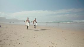 Surfers on the Beach. Daytona Beach, USA - September 1, 2016: Pro Surfers getting ready for riding waves on the beach on a sunny day on September 1, 2016 stock footage