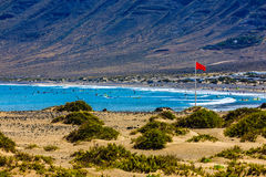 Surfers beach Famara always has a red flag. Surfers beach Famara on Lanzarote always has a red flag Stock Photos