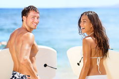 Surfers on beach having fun in summer. Surfer women and men with boogieboard smiling happy on beach on Hawaii. Multiracial couple Asian women and Caucasian men Stock Photo