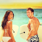 Surfers on beach having fun in summer. Surfer women and men with boogieboard smiling happy on beach on Hawaii. Multiracial couple Asian women and Caucasian men Stock Photography