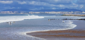 Surfers in the beach with Lisbon in background. Costa da Caparica, Portugal. April 19, 2015: Surfers in the beach with Lisbon in background. This is an iconic Stock Photos