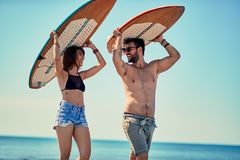Surfers at the beach- Young couple of surfers walking on the beach and having fun in summer Vacation. Extreme Sport. Surfers at the beach- Smiling young couple stock photos