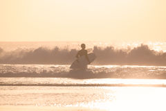 Surfers on beach with surfboard. Male surfers on sandy beach with the surfboard in sunset Stock Photo