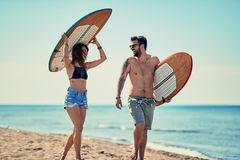 Surfers at the beach- Young couple of surfers walking on the beach and having fun in summer. Surfers at the beach- Smiling young couple of surfers walking on royalty free stock photo