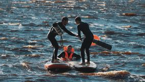 Surfers beating each other with big soft batons to push opponent into water. Two surfers wearing black full swimsuit beating each other with big soft batons to stock footage