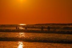 Surfers bij de zonsondergang Stock Foto's