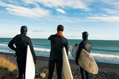 Surfers on the black sand beach in Iceland. Three surfers young man standing on the black sand beach in Iceland and looking at the ocean waves Royalty Free Stock Photo