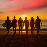 Surfers boys and girls group walking on beach. Surfers teen boys and girls group walking on beach at sunshine sunset backlight royalty free stock image
