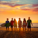Surfers boys and girls group walking on beach. Surfers teen boys and girls group walking on beach at sunshine sunset backlight stock images