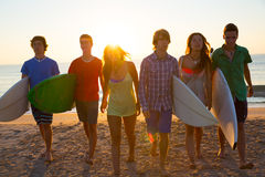 Surfers boys and girls group walking on beach Royalty Free Stock Photos