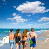 Surfers boys and girls walking rear view on beach Stock Image