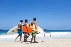 Surfers brésiliens marchant sur la plage Rio d'Ipanema Image libre de droits