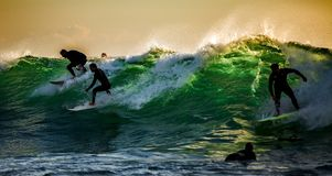 Surfers in breker Stock Foto's