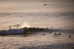 Surfers catch the evening waves in the ocean. The view from the top. Bali Indonesia Royalty Free Stock Images