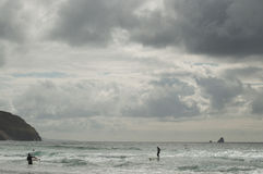 Surfers on a cloudy day Royalty Free Stock Photography