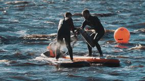 Surfers compete beating each other with soft batons to push opponent into water. Two surfers wearing black full swimsuit beating each other with big soft batons stock video
