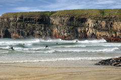 Surfers competition near cliffs Stock Images