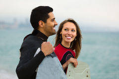 Surfers couple on the beach Stock Photography