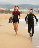 Surfers couple on the beach Stock Images