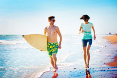 Surfers couple running on the seashore Stock Images