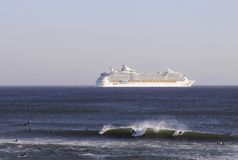 Surfers and Cruise Ship on the Horizon Royalty Free Stock Images