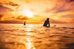 Surfers dans l'océan au coucher du soleil ou au lever de soleil Couples de surfer et d'océan Images stock