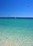 Surfers de vent et de cerf-volant dans le cristal - mer claire avec le ciel bleu ensoleillé lumineux. photographie stock