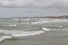 Surfers in Denmark, the sea is turbulent. LOKKEN, DENMARK - JULY 9, 2016: Surfers in the turbulent sea. On the beach of Lokken, Denmark Royalty Free Stock Images