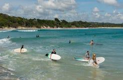 Surfers die golven in het strand van Byron Bay zoeken Stock Afbeelding